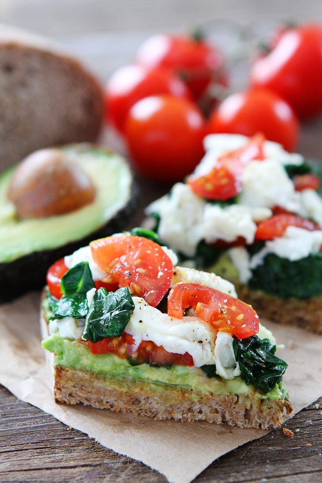 Avocado Toast with Eggs, Spinach, and Tomatoes from twopeasandtheirpod.com on foodiecrush.com