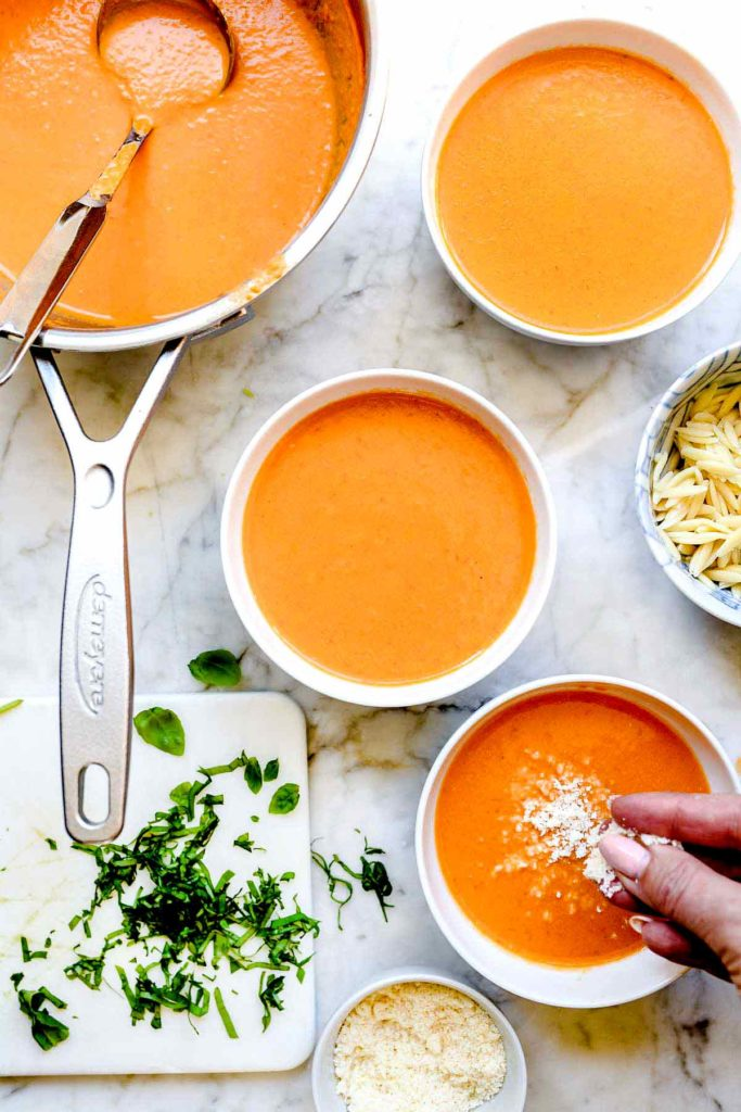 garnishing bowls of tomato basil soup with Parmesan cheese