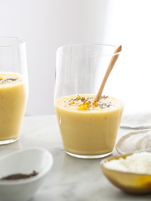 mango smoothie in glass garnished with mango chunks and chia seeds