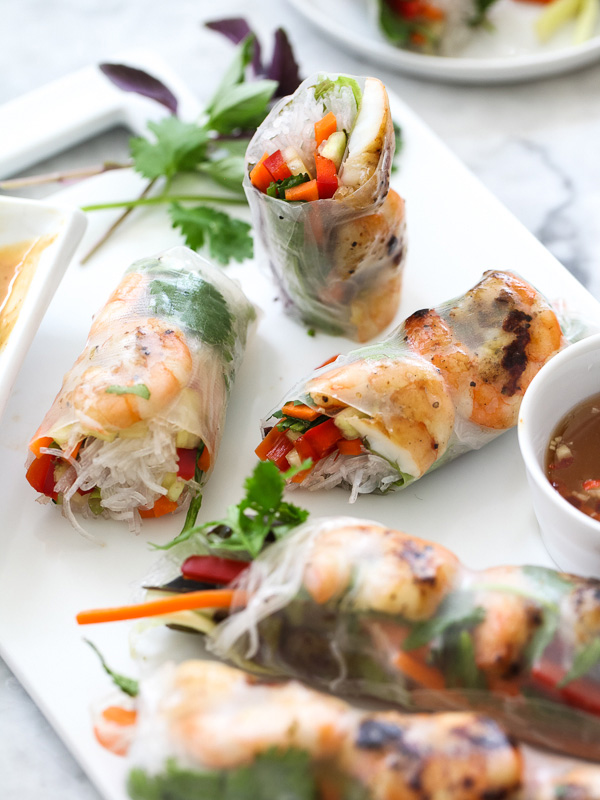 Grilled shrimp spring rolls on white platter
