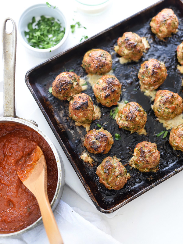 tray of baked turkey meatballs next to pot of tomato sauce
