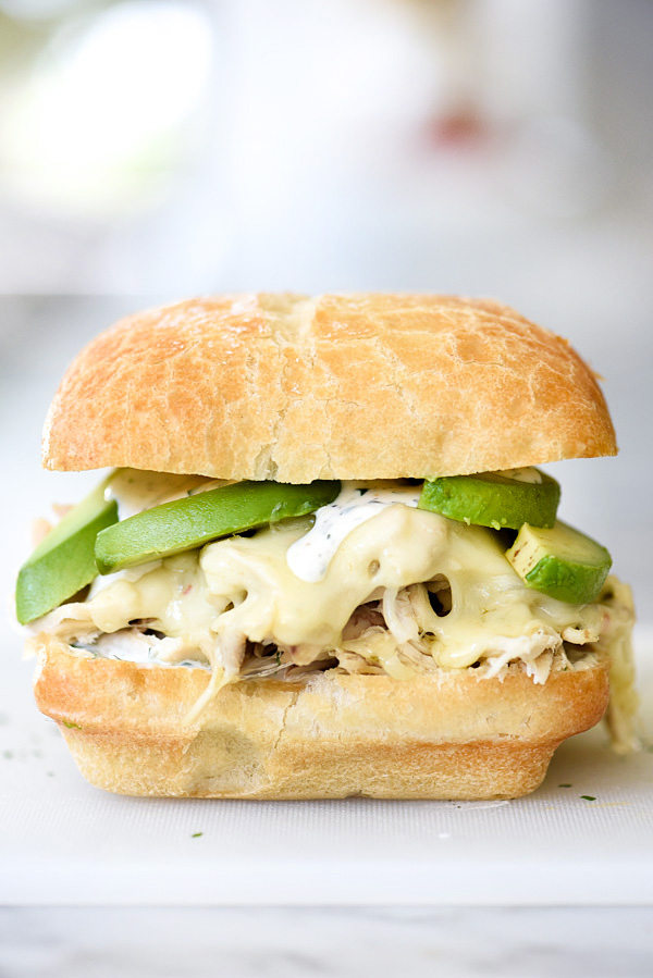pulled chicken sandwich topped with avocado and ranch sauce