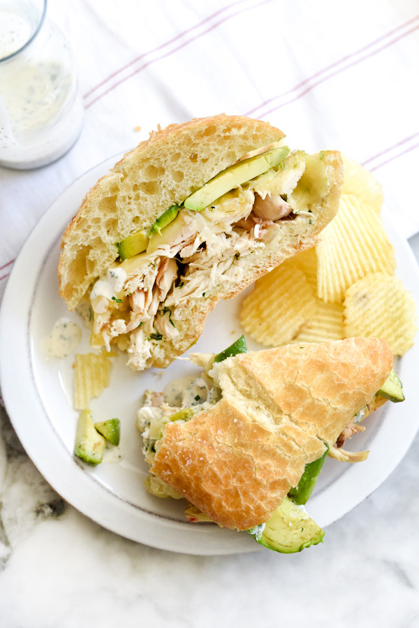 Shredded Chicken Sandwich with Ranch Sauce and potato chips on plate