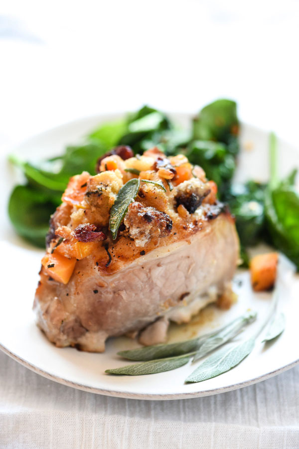 stuffed pork chop on white plate with fresh sage leaves