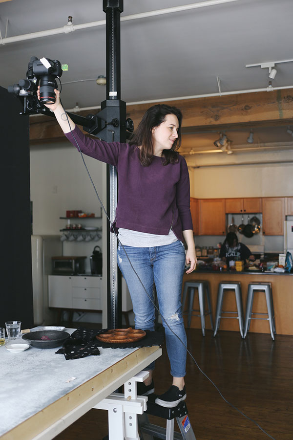 woman prepping lights for cookbook photo shoot