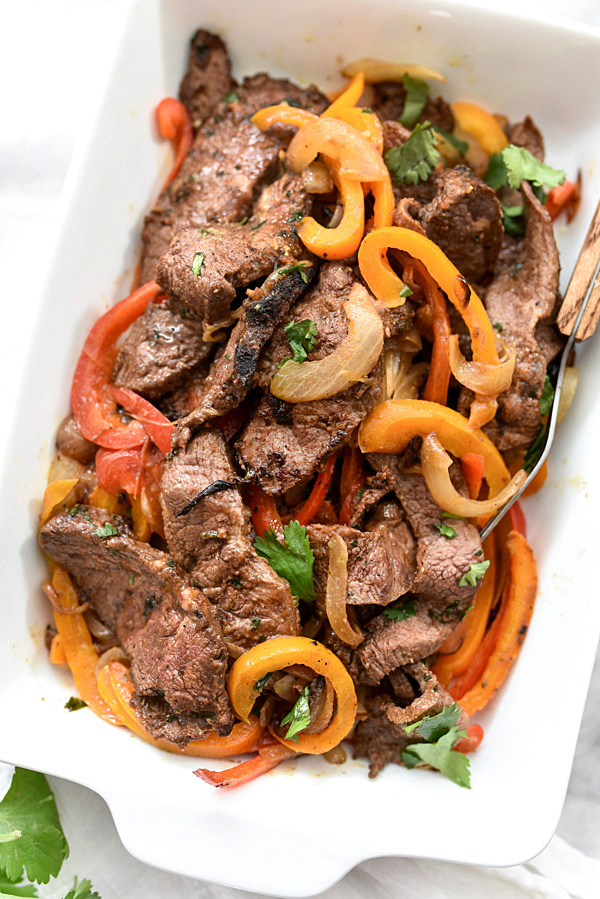 steak fajitas in white serving dish