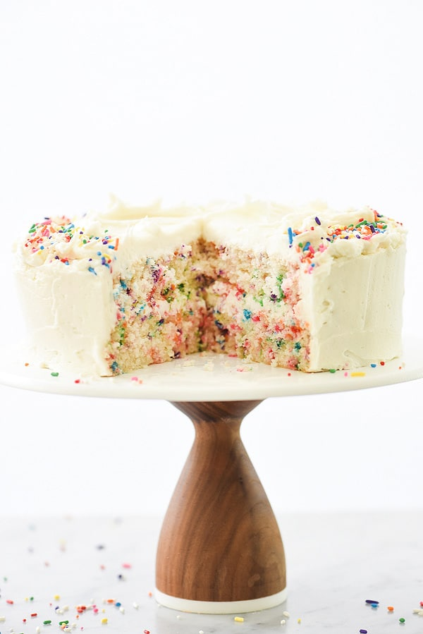 sliced confetti cake on cake stand frosted with homemade buttercream frosting