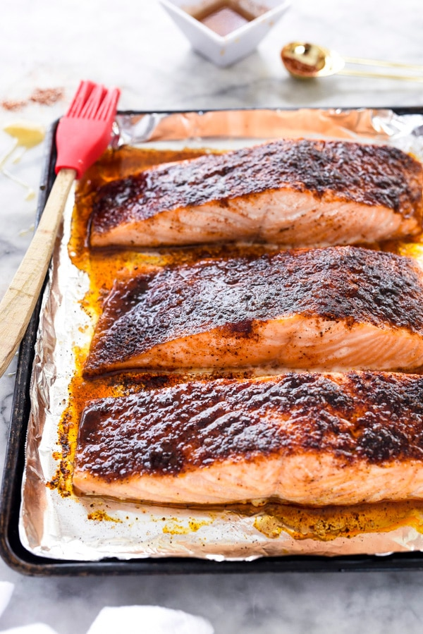 three maple glazed salmon fillets on baking sheet