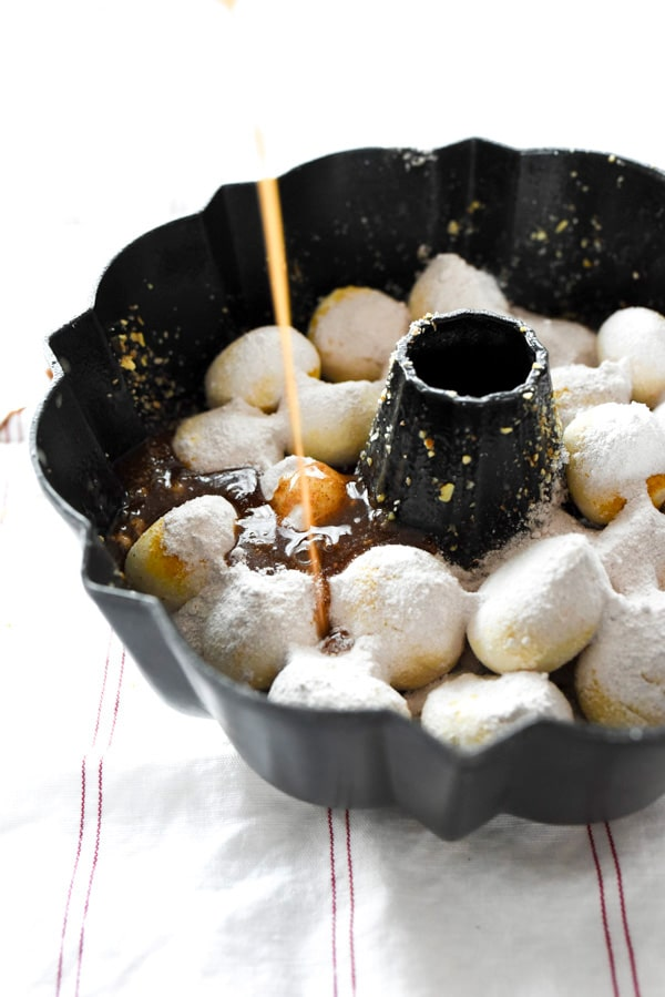 pouring melted butter over uncooked cinnamon monkey bread