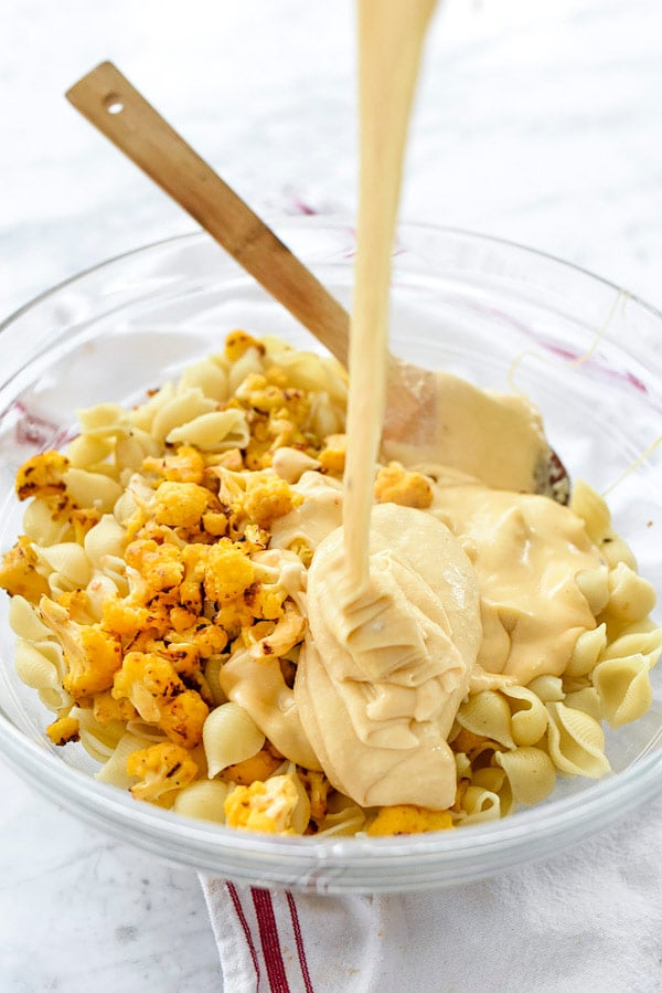 pouring cheese sauce into bowl of cooked pasta and cauliflower