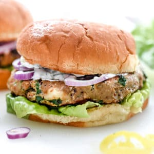 Greek Turkey Burgers with Tzatziki Sauce are packed with fresh spinach, sun-dried tomatoes, oregano and feta cheese for a healthy Mediterranean version for hamburger fans | foodiecrush.com