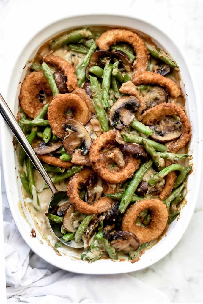 homemade green bean casserole in white baking dish with spoon