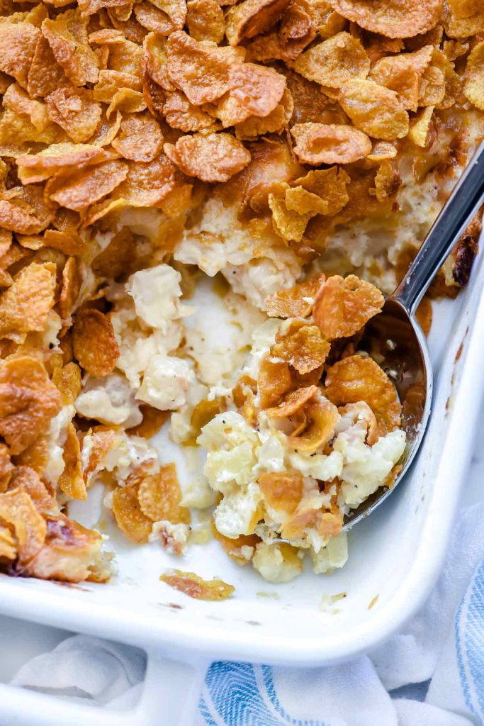 Funeral potatoes in baking dish with spoon