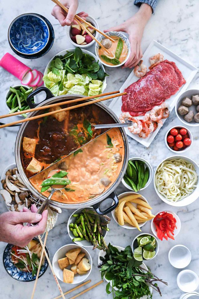 assortment of hot pot broths, vegetables, and proteins on marble counter
