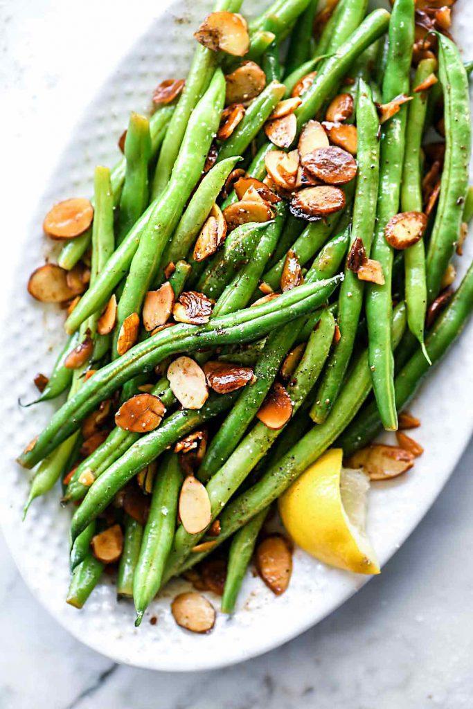green beans almondine on white platter with lemon wedge