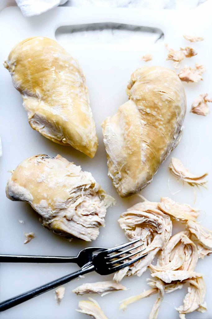 three instant pot chicken breasts on countertop with two forks
