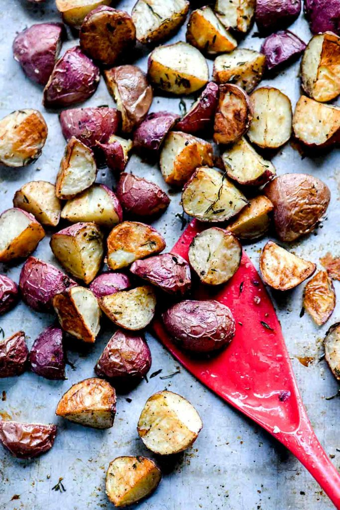 oven roasted red potatoes on baking sheet with red spatula
