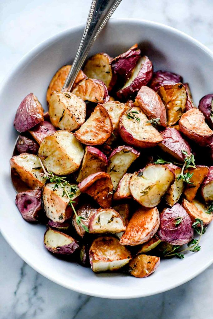 crispy roasted potatoes in white bowl with spoon