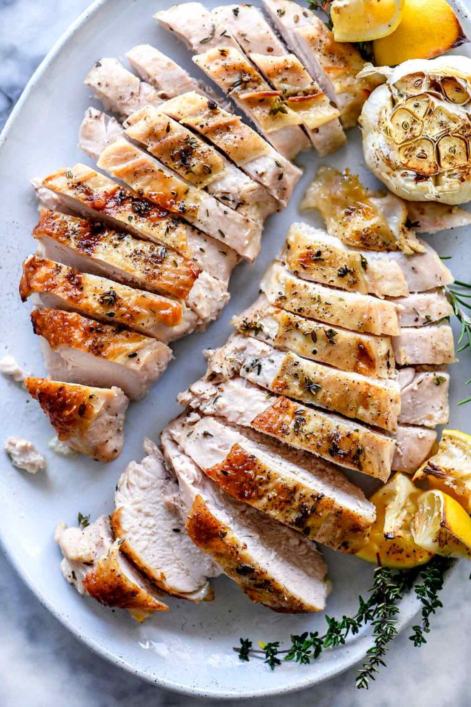 sliced roast turkey breast on white platter with roasted clove of garlic and fresh herbs