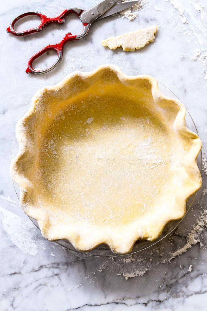 crimped butter pie crust in glass pie plate