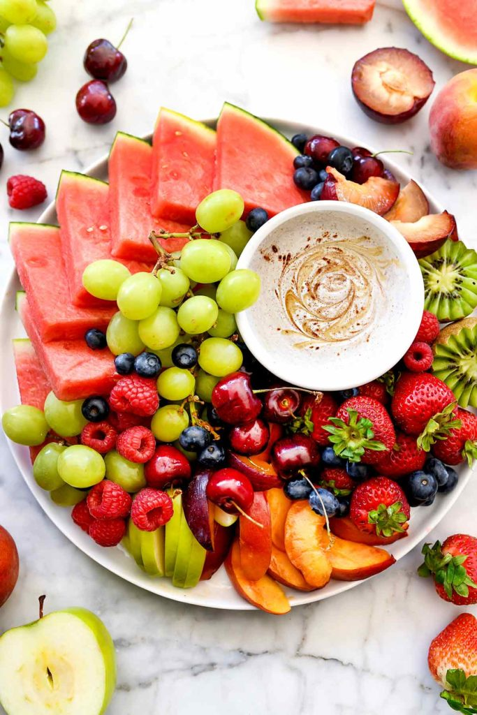 platter of fresh fruit with bowl of fruit dip in the center