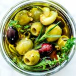 Marinated Olives Recipe with herbs in jar foodiecrush.com